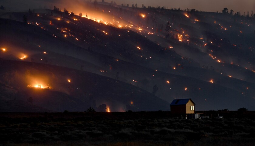 A solitary building stands in the foreground as the Lake fire burns in the hills of the Angeles National Forest behind it
