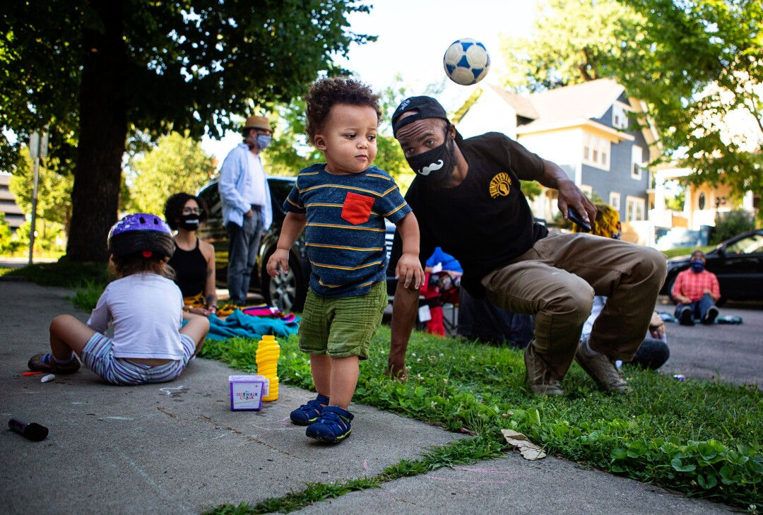 A toddler plays with a ball as his father watches at a community gathering led by Alicia Smith in Minneapolis