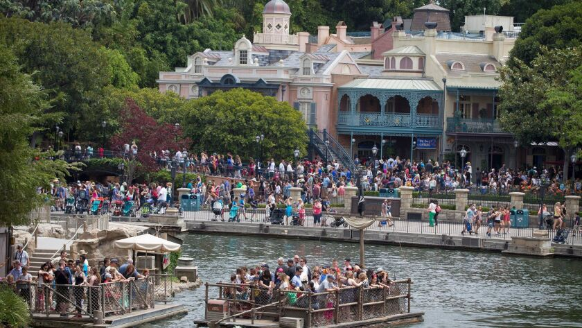 Crowds fill rafts to Tom Sawyer Island with New Orleans Square in the background in this 2015 photo.
