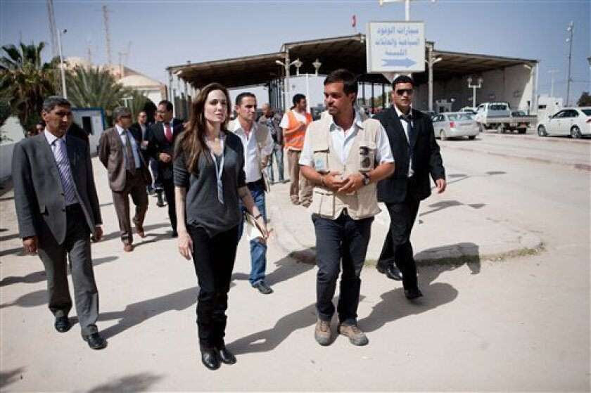 United Nations High Commissioner for Refugee goodwill ambassador Angelina Jolie, center left, walks with UNHCR Protection Officer Patrick Mansour, second from right, at the Ras Djir Tunis-Libyan border on Tuesday, April 5, 2011. Jolie traveled on Tuesday morning to the Tunisian-Libyan border to urge greater international support for people fleeing Libya. (AP Photo/UNHCR, Jason Tanner)