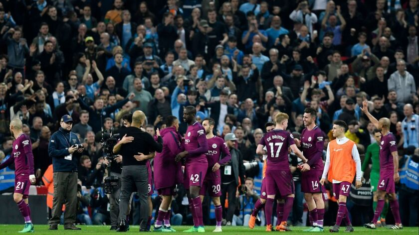 Manchester City players and fans celebrate after the English Premier League soccer match Tottenham Hotspur vs Manchester City at Wembley Stadium in London, Britain on April 14.