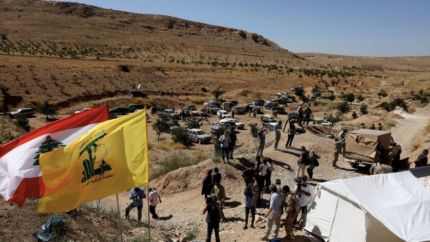 Lebanese and foreign media are seen in front of the entrance to a cave used by Al Nusra fighters in a mountainous area near Arsal at the Lebanese-Syrian border on July 29, 2017.