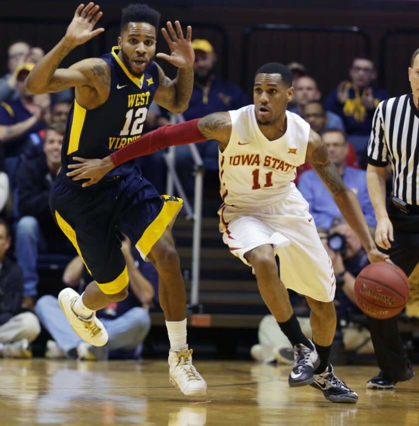 Iowa State guard Monte Morris (11) drives up court while being guarded West Virginia guard Tarik Phillip (12) during the first half of an NCAA college basketball game, Monday, Feb, 22, 2016, in Morgantown, W.Va. (AP Photo/Raymond Thompson)