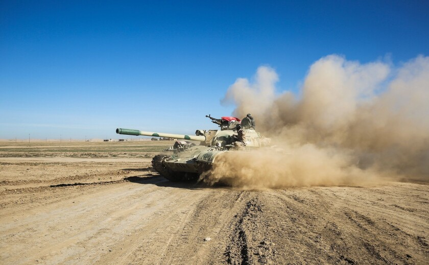 Iraqi tanks and armored vehicles advance toward the village of Sheikh Younis, south of Mosul, on Feb. 19