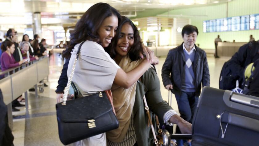 Abeer Abdelrahman, left, hugs sister Areej Ali at the Tom Bradley International Terminal at LAX after Ali's arrival from Sudan.