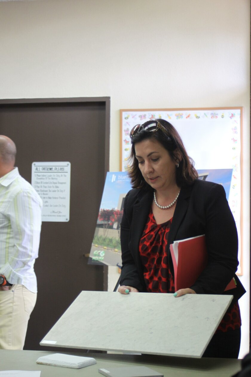Applicant Elizabeth Carmichael shows material samples for the home build project at 311 Sea Ridge Drive.