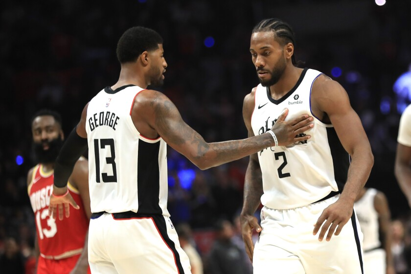 Clippers' Kawhi Leonard is congratulated by Paul George during the second half against the Houston Rockets at Staples Center.