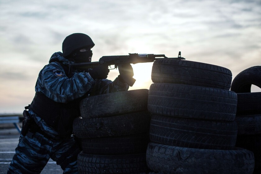A pro-Russia service member stands guard at a checkpoint in Chongar, blocking an entry point into Crimea, southern Ukraine.