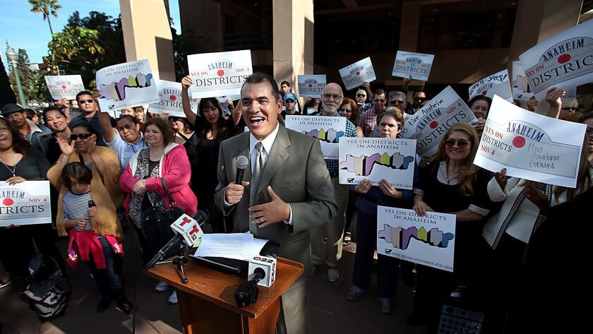 Jose Moreno is joined by members of the community at a news conference in 2014 to announce an agreement with the Anaheim mayor and City Council to put the issue of district elections on the ballot later that year. Moreno was elected to the council last November.