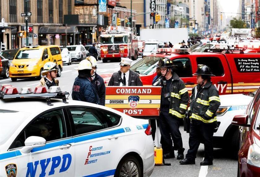 Agentes de policía y del cuerpo de bomberos trabajan en la 8 Avenida, cerca de una oficina postal donde se encontró otro paquete sospechoso, en Nueva York. EFE/Archivo