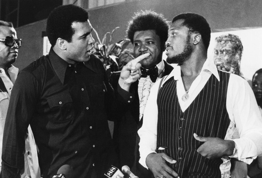 FILE - In this July 17, 1975, file photo, sports promoter Don King stands between Muhammad Ali, left, the heavyweight champion, and Joe Frazier in New York. Ali, the magnificent heavyweight champion whose fast fists and irrepressible personality transcended sports and captivated the world, has died