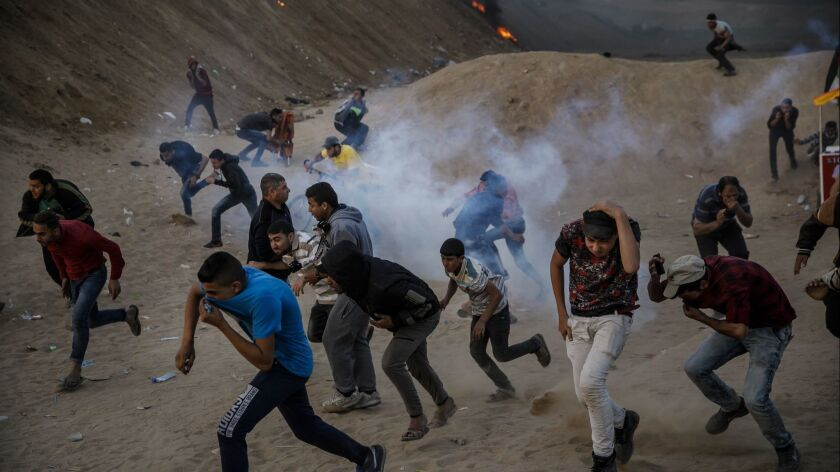 Protesters scatter from tear gas during a border protest in Bureij, Gaza.