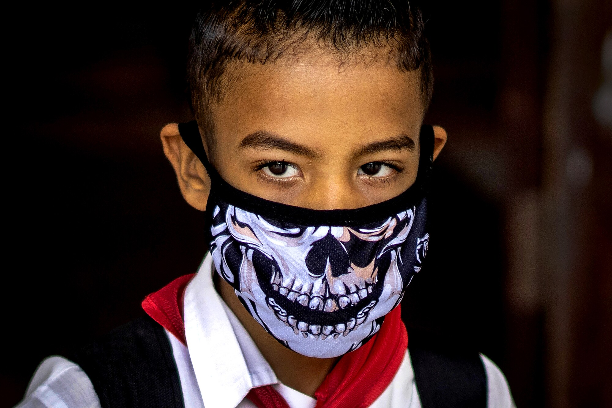 CUBA: A student in Havana wears a skull face mask as a precaution against the spread of the coronavirus as he leaves school for the day.