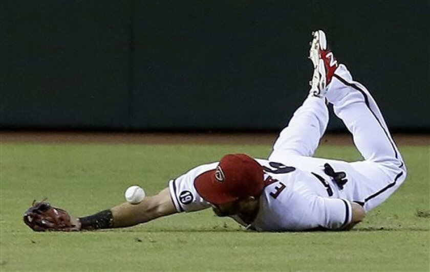 Arizona Diamondbacks' Adam Eaton dives but is unable to come up with a single, good for two runs batted in, hit by Colorado Rockies' Wilin Rosario in the first inning of a baseball game on Friday, Sept. 13, 2013, in Phoenix. (AP Photo/Ross D. Franklin)