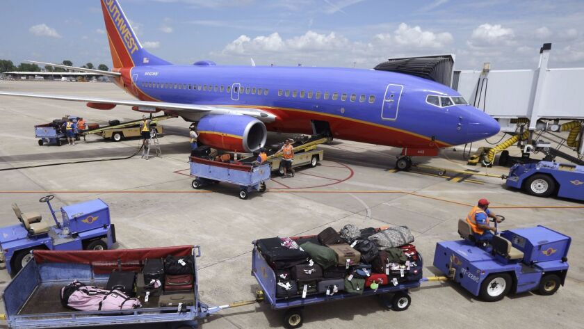 Baggage carts are towed to a Southwest Airlines jet at Bill and Hillary Clinton National Airport in Little Rock, Ark. The CEO of the airline said he will not consider charging a bag fee to raise revenues.