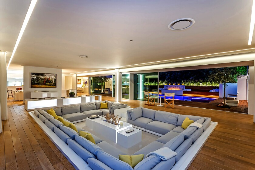 The single-story house, built in 1960, evokes a Miami night club with an all-white interior, a sunken conversation pit and custom LED lighting.