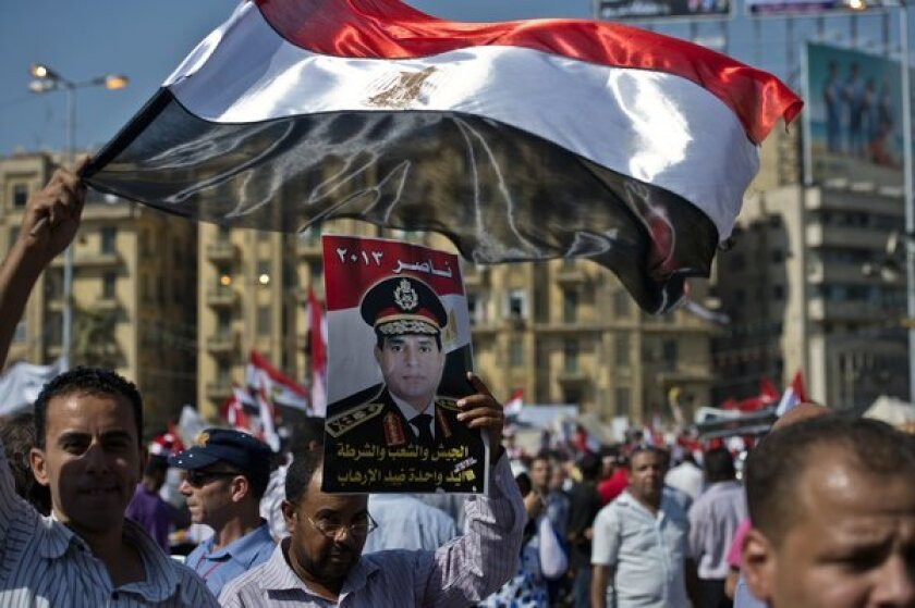 Supporters of army chief General Abdel Fattah Sisi carry his portrait and wave the Egyptian flag in Cairo's Tahrir Square.