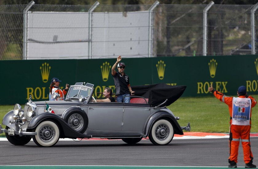 Force India driver Sergio Perez of Mexico waves to the crowd as he rides on a classic car before the Formula One Mexico Grand Prix auto race at the Hermanos Rodriguez racetrack in Mexico City, Sunday, Nov. 1, 2015. (AP Photo/Eduardo Verdugo)