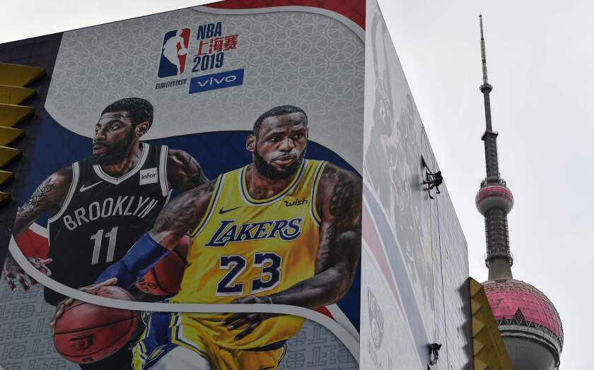 A worker removes a promotional banner from a building in Shanghai on Wednesday promoting a scheduled exhibition game between the Lakers and Brooklyn Nets.