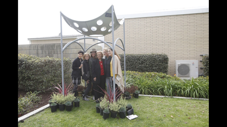 "Irma Ramirez, Charlene Ashendorf, Tracy Taber, Carolyn McDemas, Councilwoman Katrina Foley and Andrea Marr stand under James McDemas' ""The Artist's Vision"" sculpture during a dedication ceremony Friday at Costa Mesa City Hall."