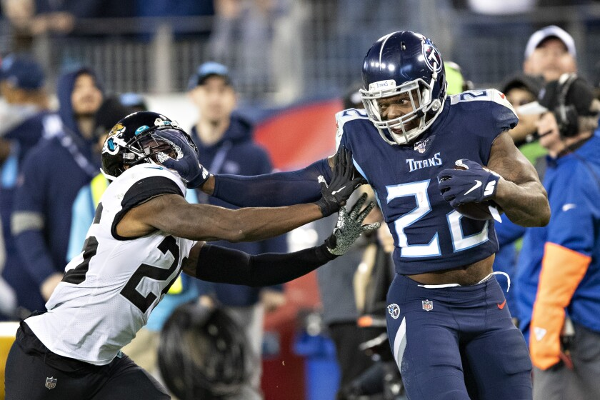 Tennessee Titans running back Derrick Henry stiff arms Jacksonville Jaguars safety Jarrod Wilson.