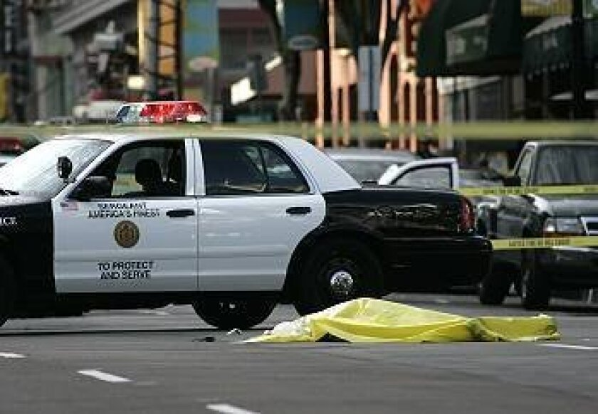 A tarp covers the body of a man shot and killed by police after a confrontation in the Gaslamp Quarter Monday.