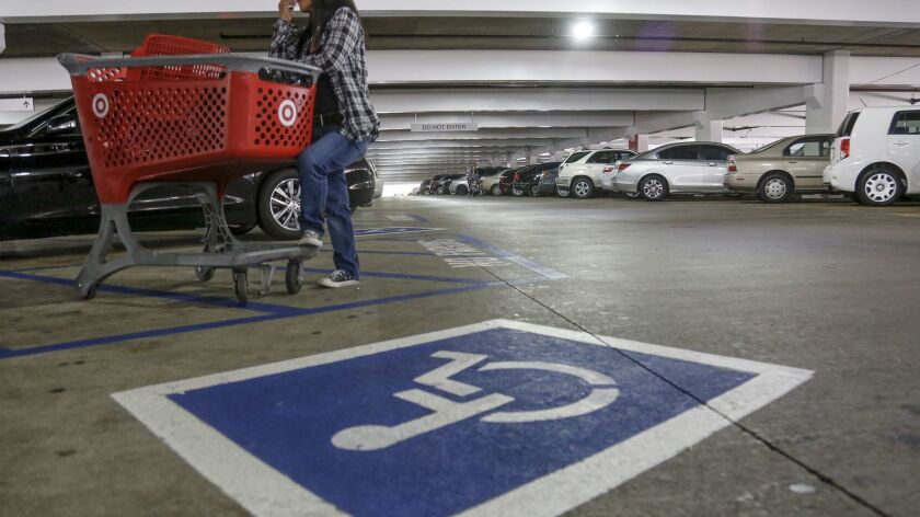 An undercover officer with the Department of Motor Vehicles waits with a shopping cart next to a disabled parking spot while conducting a sweeping enforcement of fraudulent and improper use of the disabled parking placards in the Glendale Galleria on April 11.