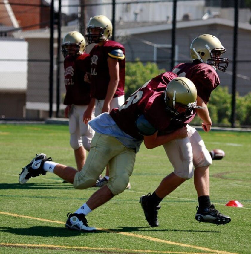 Bishop's players practice tackling.
