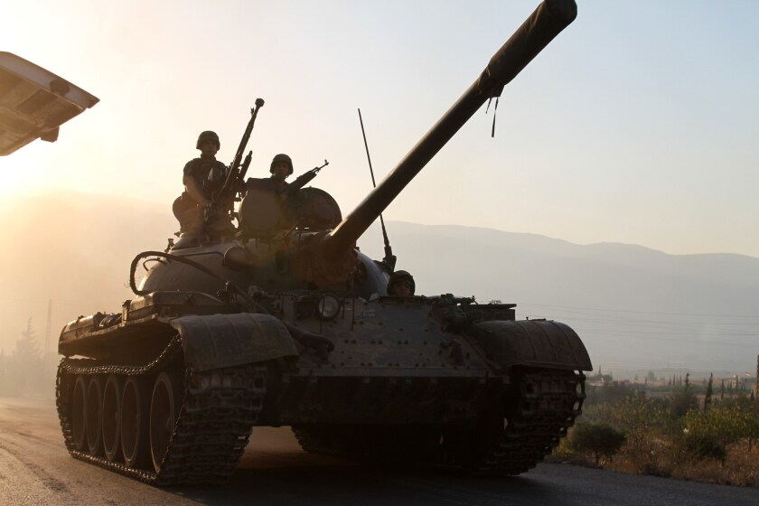A Lebanese army tank approaches the town of Arsal near the Syrian border to help secure the area where gunmen reportedly killed two soldiers after clashes erupted following the arrest of a Syrian linked to an Islamist militant group.