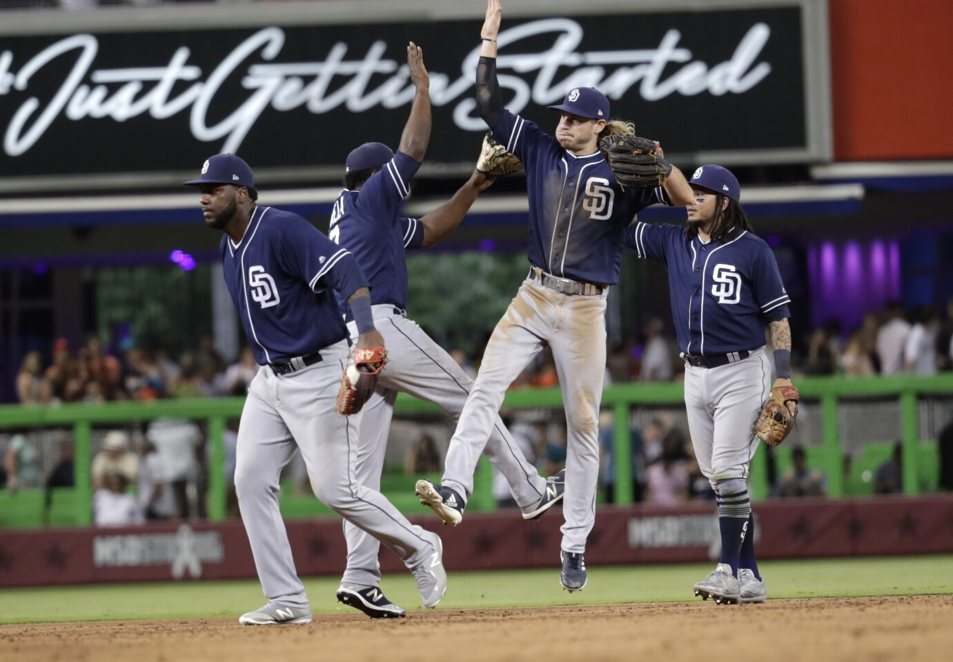 San Diego Padres left fielder Travis Jankowski, second from right, high fives second baseman Jose Pirela, second from left, after defeating the Miami Marlins 5-4 in a baseball game, Saturday, June 9, 2018, in Miami. (AP Photo/Lynne Sladky)