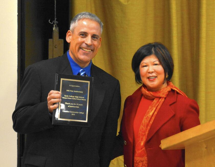 David Martinez, principal of Early College High School in Costa Mesa, receives a plaque from Coastline Community College President Lori Adrian during the high school's 10th-anniversary celebration last month.