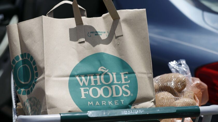 FILE - In this Friday, June 16, 2017, file photo, groceries from Whole Foods Market sit in a cart be