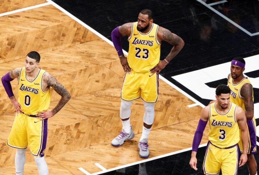 Kyle Kuzma (i), LeBron James (2i), Josh Hart (2d) y Kentavious Caldwell-Pope (d) de los Lakers reaccionan durante un partido de la NBA. EFE/Archivo