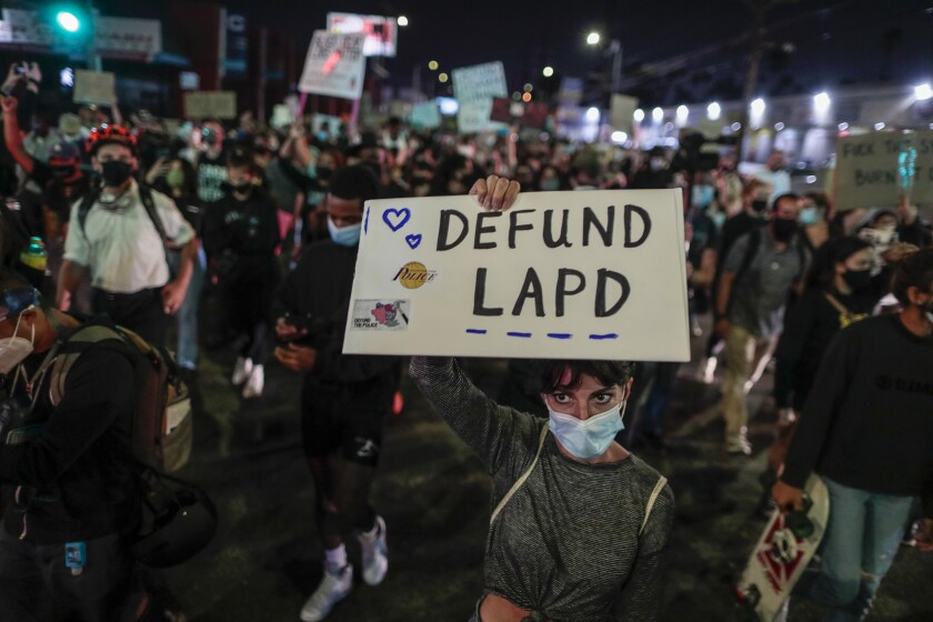 """In a crowd, a protester holds up a """"Defund LAPD"""" sign."""