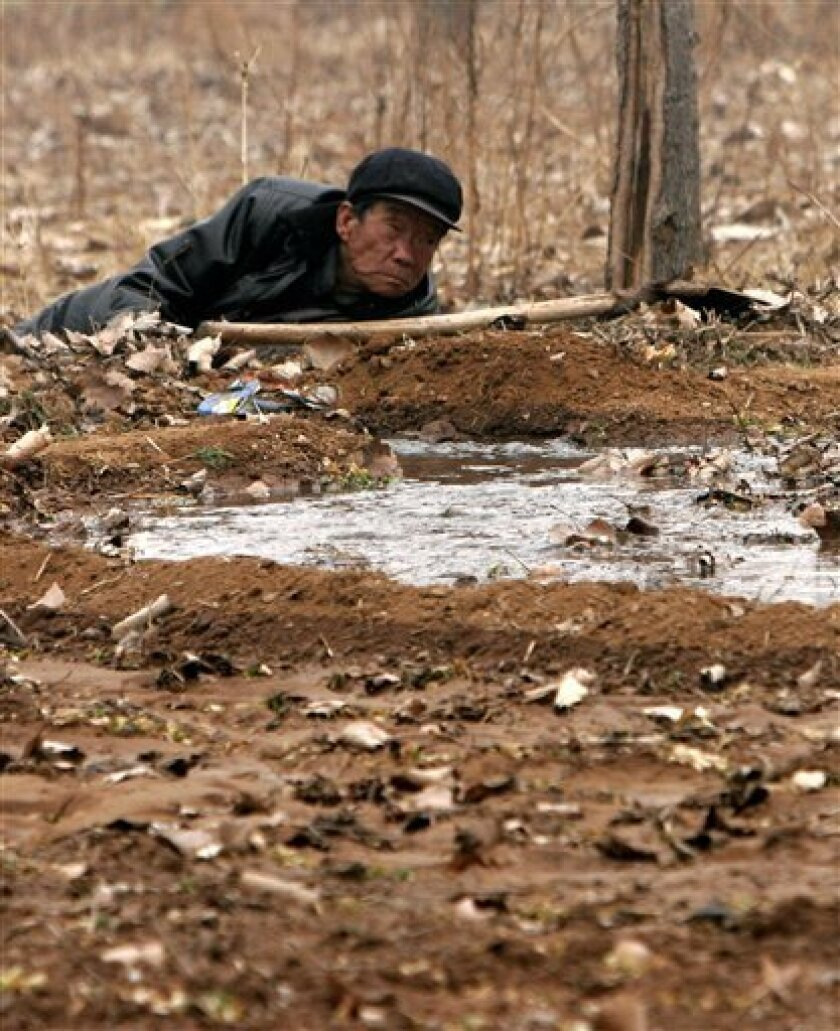 A farmer rests beside a small canal he dug to channel water released from the Luhun Reservoir to his field of rapeseed in Song county in central China's Henan province Friday Feb. 6, 2009. He came to his field at 3.00 am in preparation for the release of the water. China will give US$12 billion to help wheat-growing communities across the country's northern region survive their worst drought in five decades, state media reported Saturday. (AP Photo)