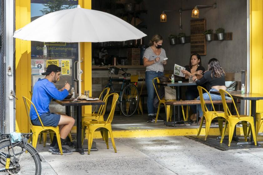 Una mesera toma una orden a un par de clientes mientras otro almuerza en el exterior en el restaurante Ginger and Lemongrass, el miércoles 30 de septiembre de 2020, en Nueva York. (AP Foto/Mary Altaffer)