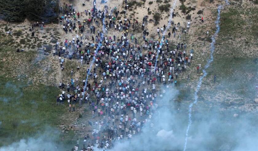Palestinos se ponen a cubierto de los disparos de soldados israelíes, en la frontera de Majdal Shams, en los Altos del Golán, cuando intentaban cruzar esta frontera entre Siria e Israel. EFE/Achivo
