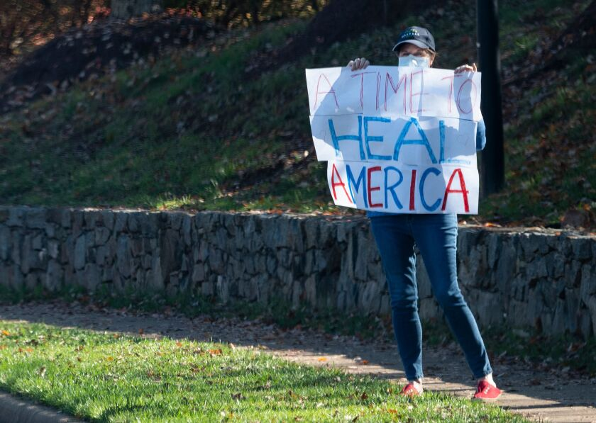 A woman holds up a sign as the motorcade of US President Donald Trump passes.