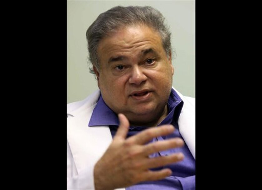 This July 20, 2009 photo shows Dr. Salomon Melgen at his office in West Palm Beach, Fla. Sen. Robert Menendez's office says he reimbursed Melgen, a prominent Florida political donor, $58,500 on Jan. 4 of this year for the full cost of two of three trips Menendez took Melgen's plane to the Dominican