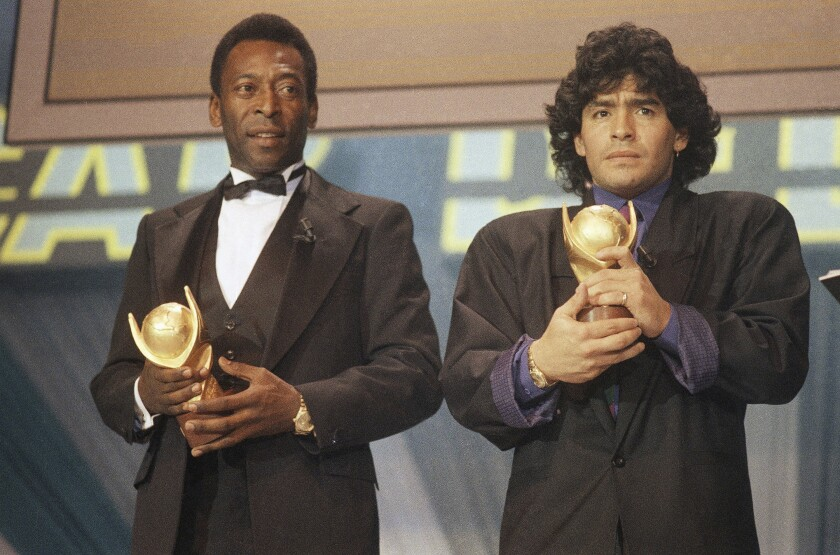 En esta foto de marzo de 1987, Pelé (izquierda) y Diego Maradona posan con sus trofeos