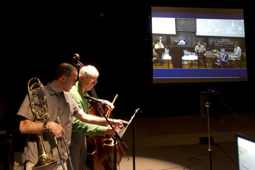 Trombonist Michael Dessen and bassist Mark Dresser work together on music as they rehearse with musicians Ray Howard, Chris Howard, Min Xiao-Fen, and Sarah Weaver, shown on a screen, background, who are at Stony Brook University in New York, as they rehearse together by internet  at UCSD in San D