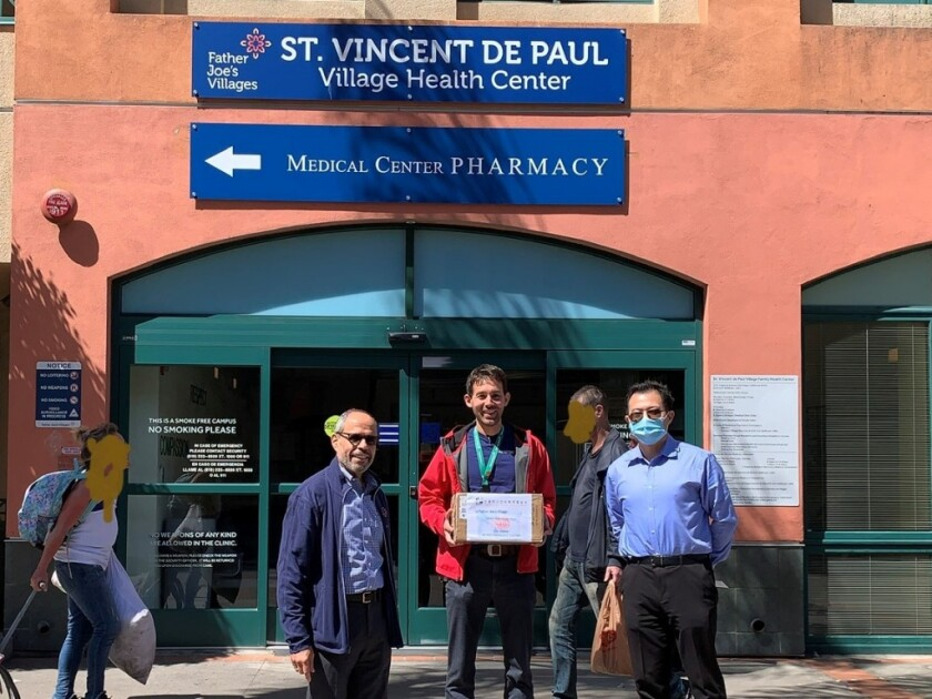 American Chinese Culture and Education Foundation President Jing Zhao (right) brings donated personal protective equipment at Father Joe's Village CEO Deacon Jim F. Vargas (left) and Medical Director Jeffrey Norris (center).