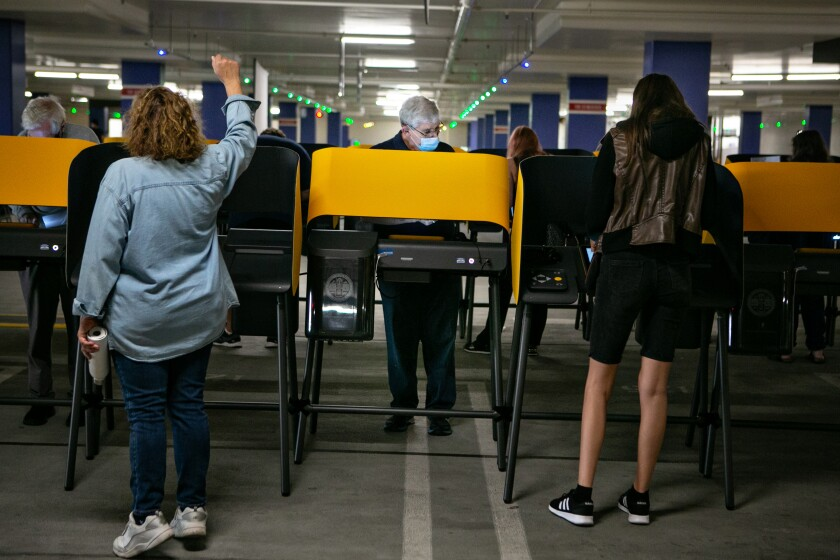 A poll worker holds her arm in the air directing a voter.