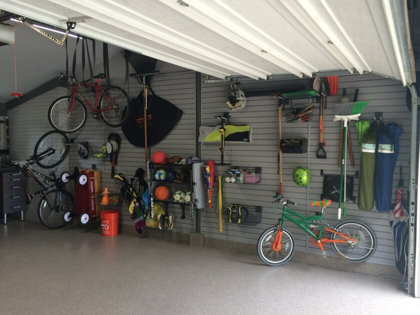 In this photo provided by Tailored Living/Premier Garage, Todd Carter of Tailored Living featuring Premier Garage decided to clean up a messy garage space to make it more attractive and useful. Carter added wall storage systems and flooring to transform the space into a workout room. (Tailored Livi