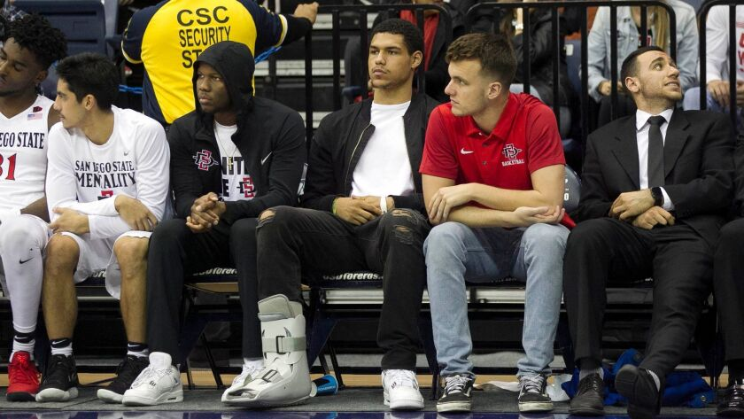 The bench has been an all-too-familiar-proposition for Trey Kell (center) this season. He sat out SDSU's game here against USD with a sprained right ankle. On Saturday vs. UNLV, he sprained his left ankle.