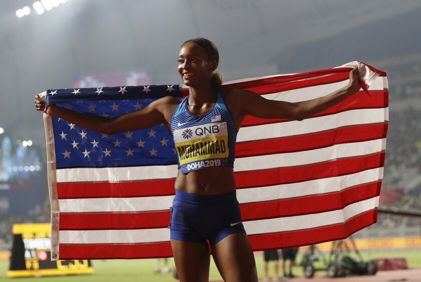 Dalilah Muhammad celebrates after setting a new world record in the 400-meter hurdles on Friday in Doha, Qatar.