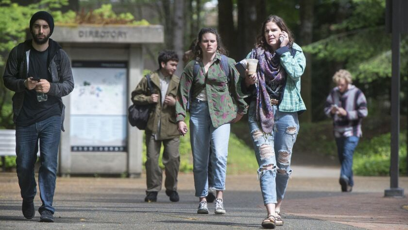 FILE - In this June 1, 2017 file photo, students leave the Evergreen State College campus in Olympia