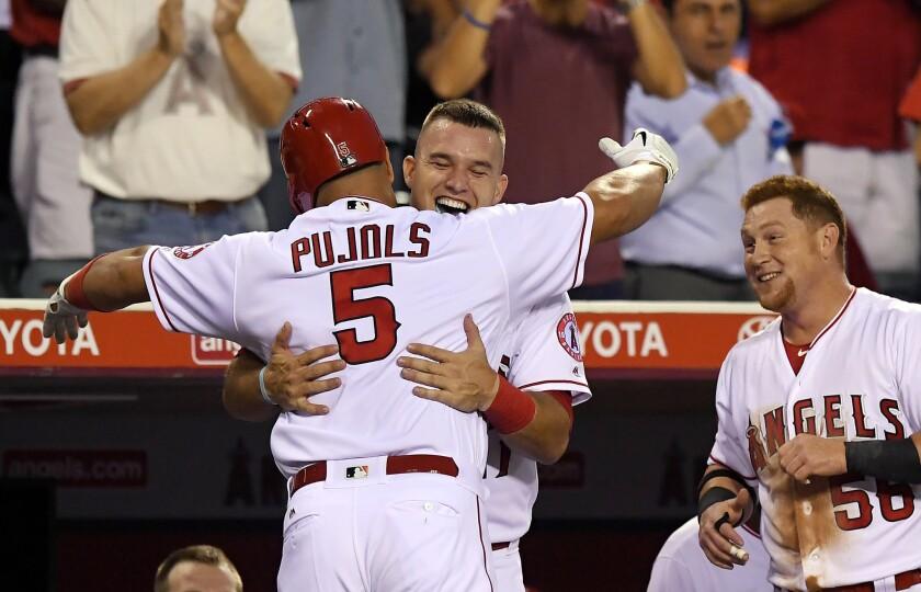 El jugador de los Angelinos de Los Ángeles Albert Pujols (izquierda), recibe la felicitación de Mike Trout (centro), ante la mirada de Kole Calhoun durante el primer inning.