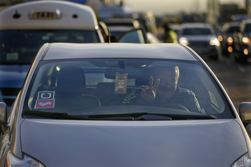 A driver for Uber and Lyft flashes a peace sign as he navigates traffic at Los Angeles International Airport in December.