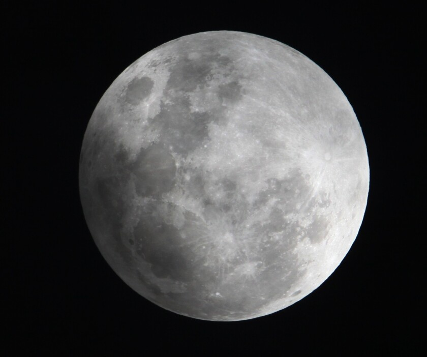 In this Monday Feb. 9, 2009 file photo, a faint shadow from the Earth is cast over part of the Moon during the penumbral lunar eclipse, seen from Manila, Philippines. Early Saturday, Feb. 11, 2017, a partial eclipse and Comet 45P will share the sky.